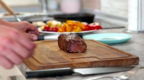 Man at Home Kitchen Slices Huge Juicy Steak Close Up. Meat Roasting Medium