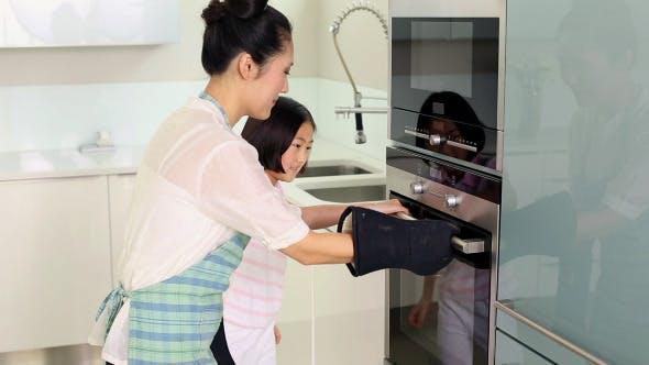 Mutter nehmen Backblech aus dem Ofen