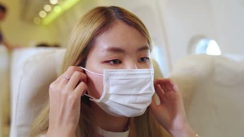 Traveler Wearing Face Mask While Traveling on Commercial Airplane