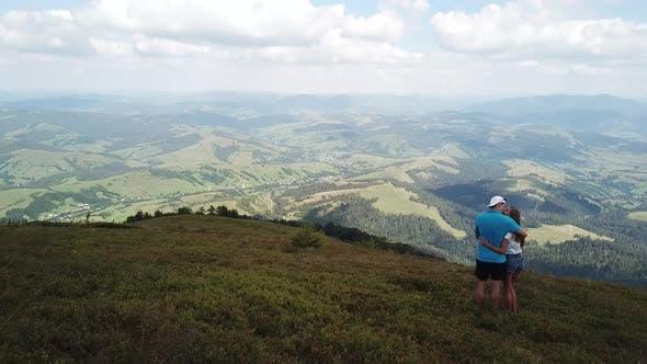 Zwei Wanderer genießen einen Blick auf die Berge.