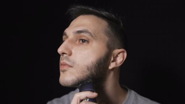 Thumbnail for Close Up of Man Trimming and Forming His Beard, Isolated on Black Background