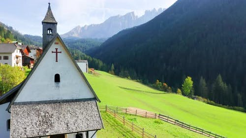 Gorgeous View Of Small Church At Green Alps With the Dolomites On The Background