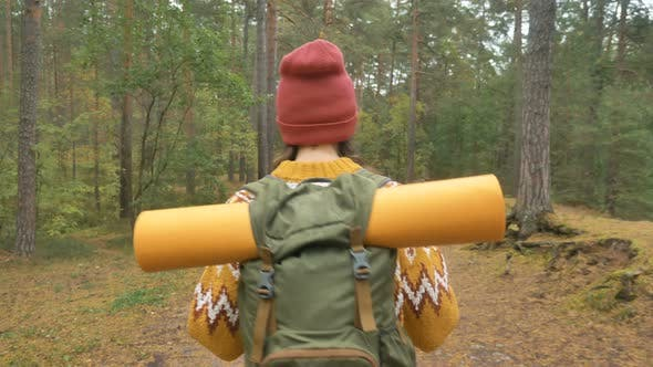 Thumbnail for Woman with Mat in Backpack Walks Along Evergreen Forest