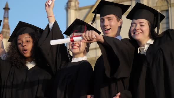 Thumbnail for Happy Young Graduate Students Showing Their Diplomas.