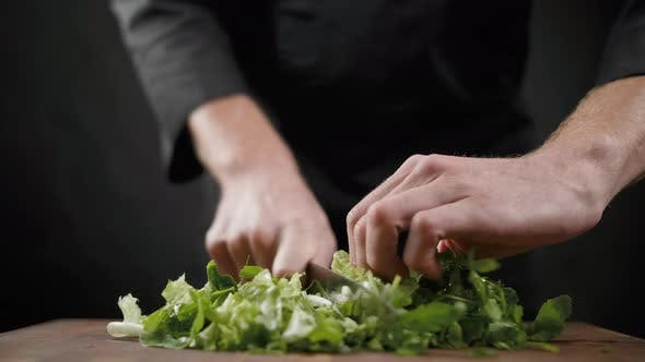 Thumbnail for Cutting a Lot of Green Lettuce for Salad on the Wooden Table on Black Background