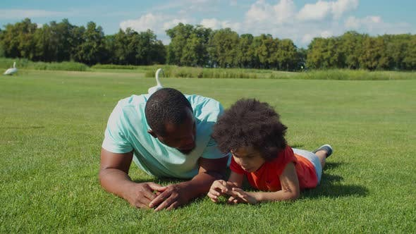 Thumbnail for African Father with Cute Son Bonding on Park Lawn