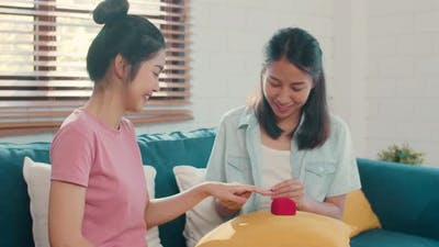 Asian Lesbian lgbtq women couple propose at home.