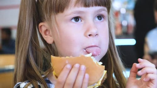 Pretty child girl eating fast food at restaurant.