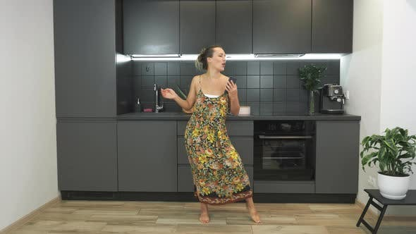 Thumbnail for Happy active funny woman is holding smartphone in hands and dancing in modern kitchen