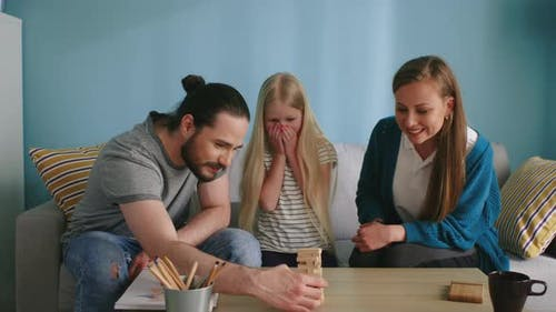 Young Family Plays Jenga at Home