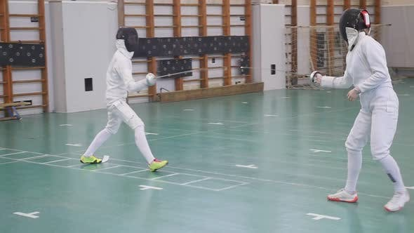 Thumbnail for Two Young Women in Full Protection Having an Active Fencing Training in the School Gym