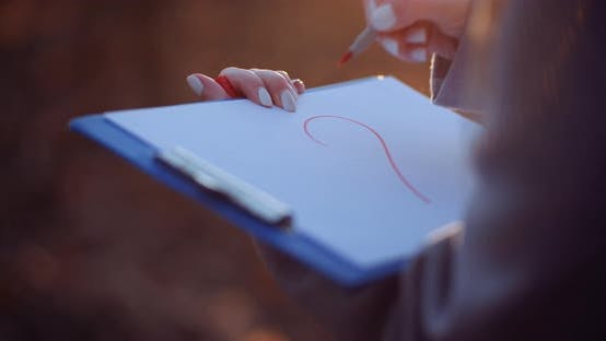 Woman Drawing Heart Symbol at Clipboard