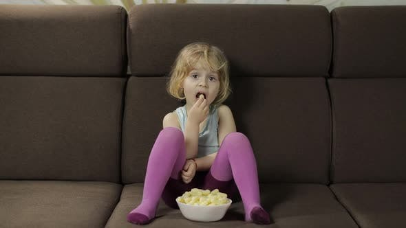 Thumbnail for Girl Sitting on Sofa and Eating Corn Puffs. Child Smiling and Taste Puffcorns