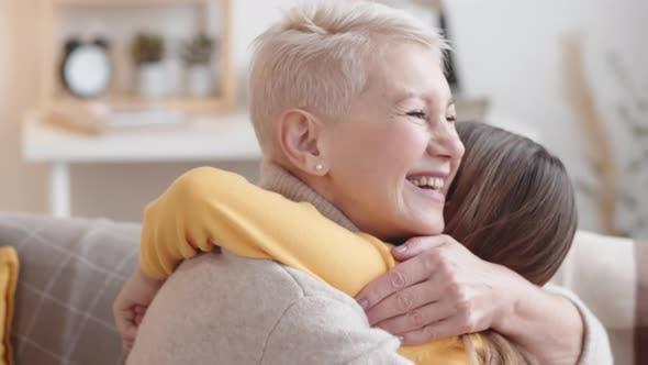 Thumbnail for Happy Caucasian Grandmother Hugging Granddaughter at Home