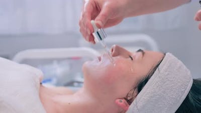 Beautician Applies Serum to to the Girls Skin