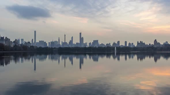 Manhattan Skyline and Reflection in Lake in Central Park at Sunset. New York City