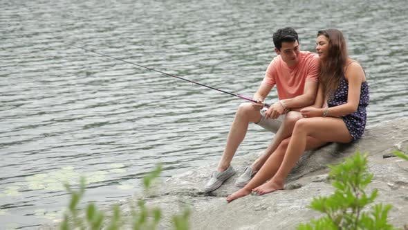 Thumbnail for Young couple fishing from rock at lakeside