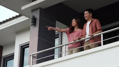 happy couple talking on balcony at home