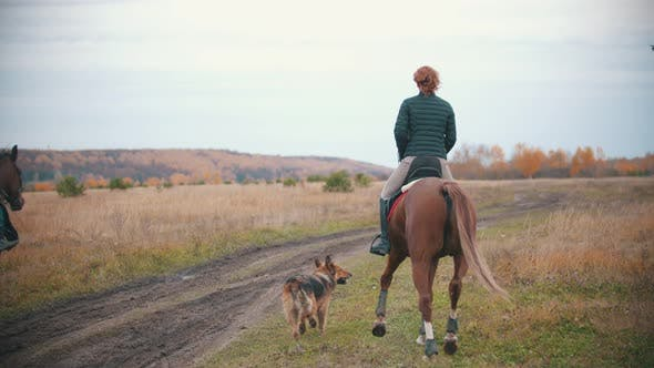 Two Women Are Riding Horses on the Autumn Field