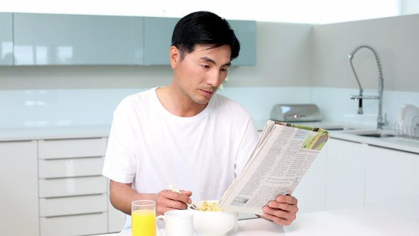 Thumbnail for Attractive Man Eating Cereal And Reading Magazine