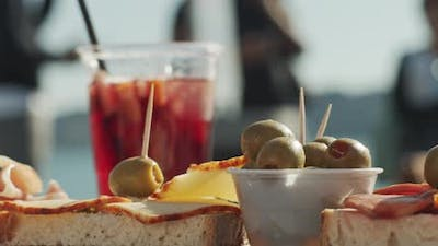 A glass of cocktail and appetizer snacks