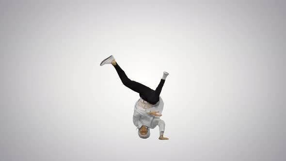 Male Doctor in White Robe and Protective Cap Dancing Breakdance on His Head and Arms on Gradient