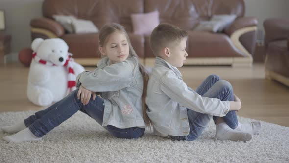 Thumbnail for Portrait Twin Caucasian Boy and Girl Sit on the Floor of Living Room Back To Back Angry To Each