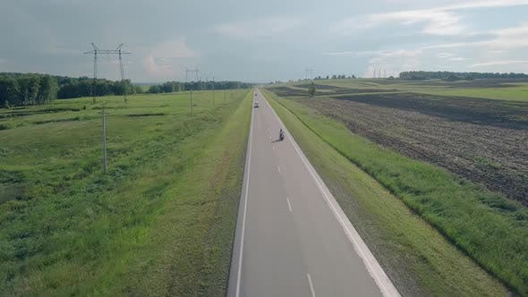 Thumbnail for Upper View People Ride Black Motorcycle Along Gray Road