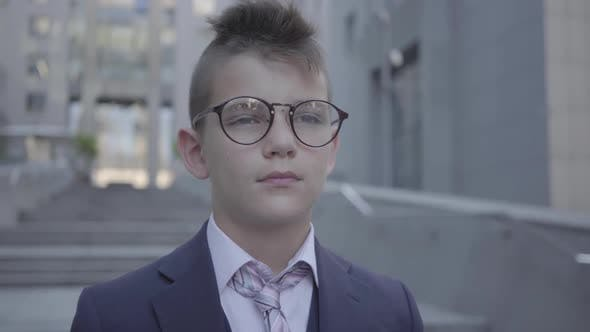 Thumbnail for Portrait Handsome Well-dressed Boy in Spectacled Standing on the Street Looking in Camera
