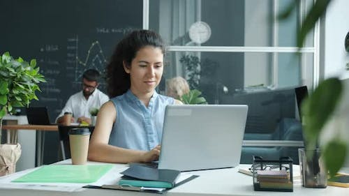Cheerful Young Woman Using Laptop Typing While Colleagues are Working in Background in Shared Office