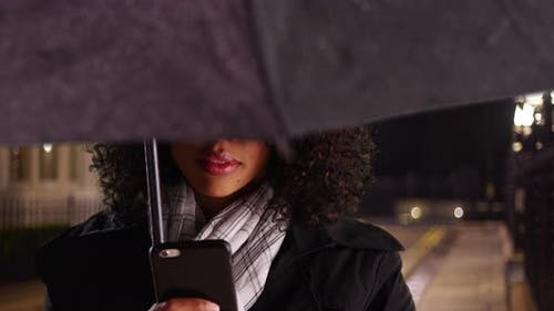 African American woman with face obscured by black umbrella using cell phone