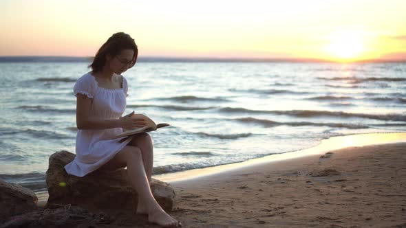 Thumbnail for A Young Woman Sits on a Stone on the Beach By the Sea with a Book in Her Hands. A Girl in a White