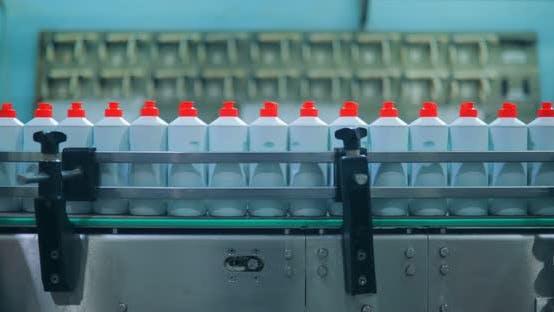 Flaschen mit weißen Plastikflaschen, die sich entlang eines Förderbandes bewegen