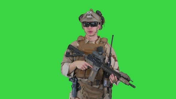 Smiling Soldier with Assault Rifle Talking on a Green Screen, Chroma Key