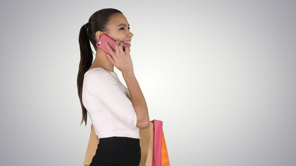 Thumbnail for Young woman walking with shopping bags talking on mobile