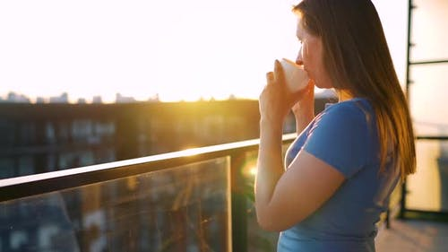Woman with a Cup of Coffee Standing on the Balcony and Admire the Sunset