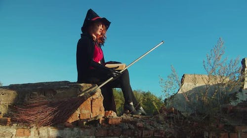 Evil Witch with Spellbook Casting Spells at Sunset
