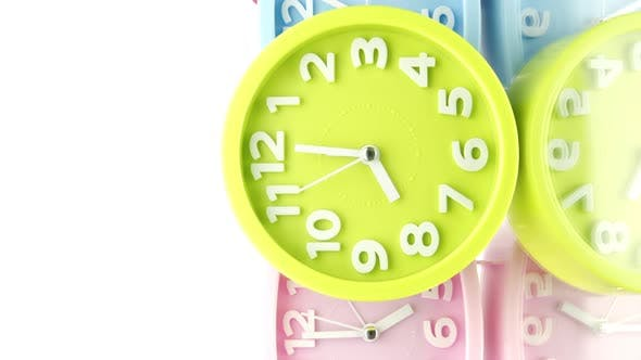 Vertical Video Colorful Alarms Ticking Show Different Times Reflecting in Glass Table