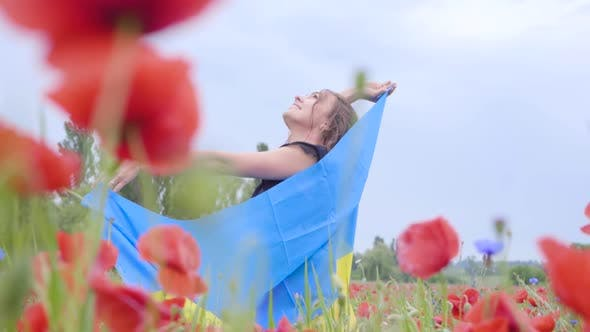 Cover Image for Cute Adorable Young Woman Dancing in a Poppy Field Holding Flag of Ukraine in Hands Outdoors
