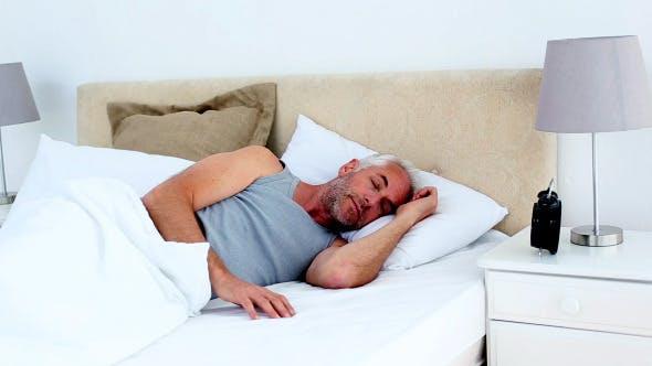 Thumbnail for Tired Man Waking Up And Looking At His Alarm Clock