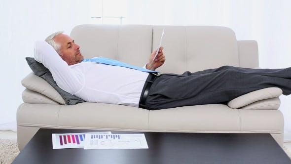 Businessman Falling Asleep Holding Paperwork