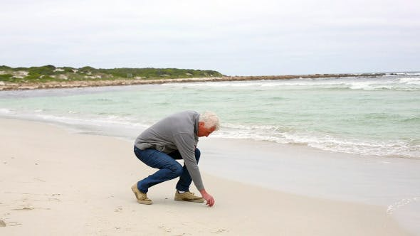 Thumbnail for Retired Man Kneeling On The Beach Looking Out