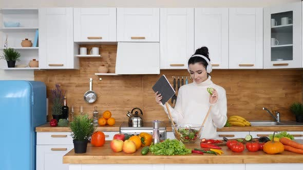 Thumbnail for Young Woman Using Tablet Computer Following Recipe To Cook Salad In Her Kitchen.