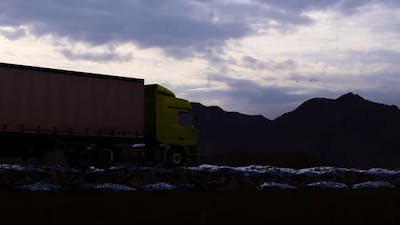 Freight Truck Moving On Rocky Path In Rainy Mountainous Evening