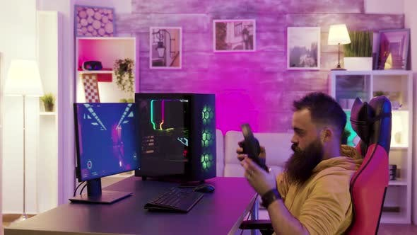 Bearded Young Man Putting His Headphones While Playing Video Games on Pc