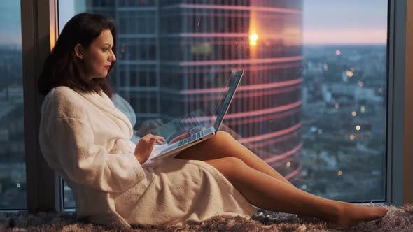 Thumbnail for Girl in Bathrobe Resting Near the Window on a High Floor in a Hotel. Girl Blogger Behind the Laptop