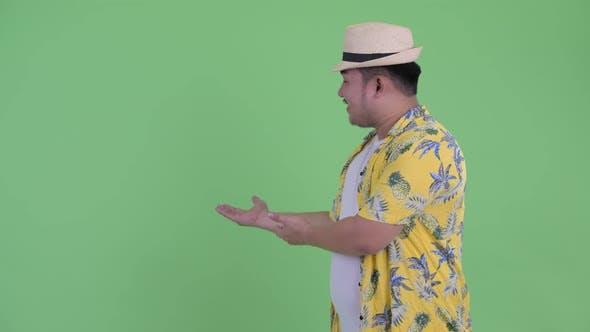 Cover Image for Happy Young Overweight Asian Tourist Man Showing To Back and Giving Thumbs Up
