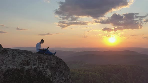 A Young Man Works on a Laptop Outdoors on a Mountaintop at Sunset.