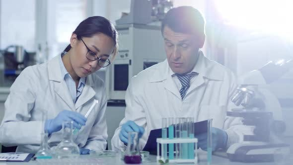 Thumbnail for Two Scientists Working with Test Tubes