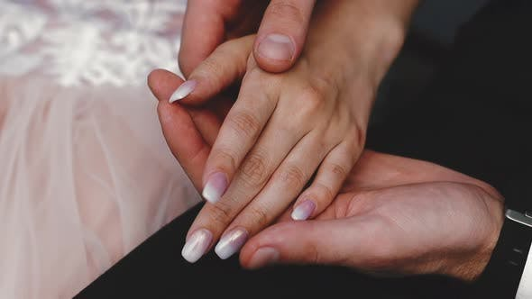 groom in suit holds hand of future wife sitting together